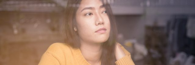 asian woman sitting alone at window contemplative