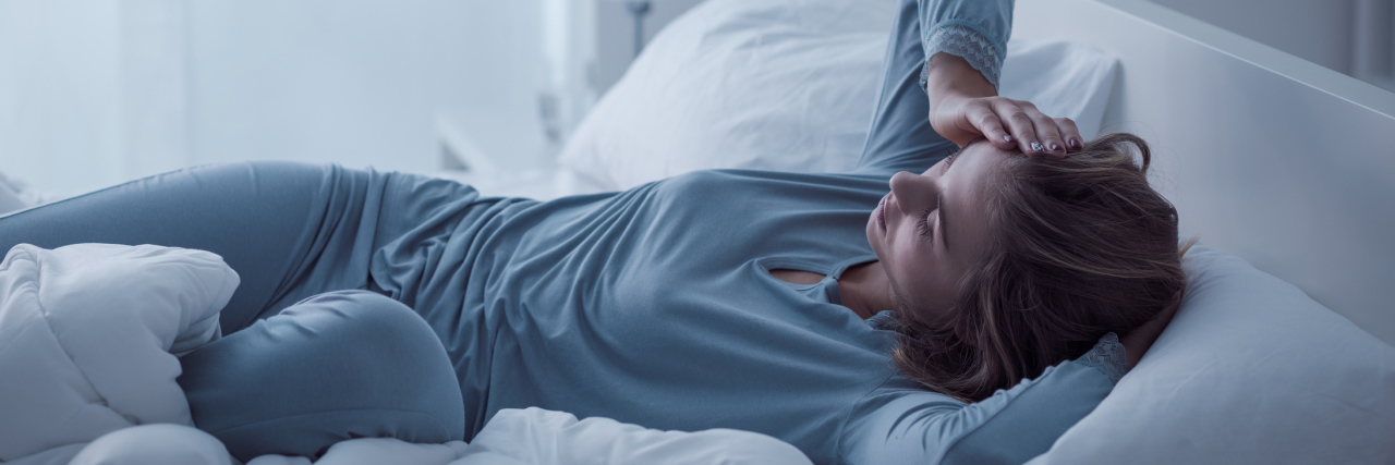 depressed woman in morning light lying in bed