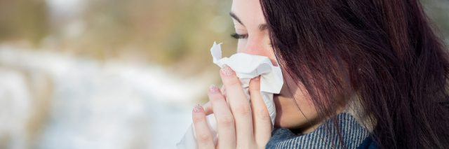 woman wearing a blue scarf and blowing her nose outside