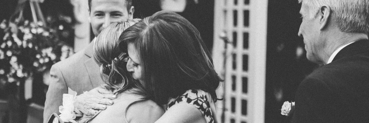 Black and white image of grown daughter hugging her mother