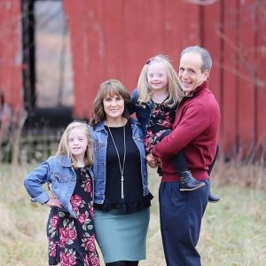 Family of four, mom and dad and two girls with Down syndrome, posing outdoors with a red barn in the background
