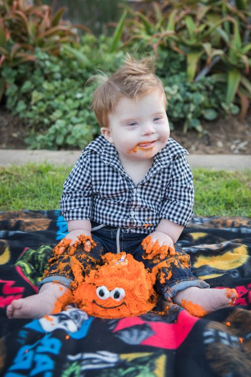Little boy with Down syndrome on his first birthday sitting outside on blanket eating a cake with orange frosting and smiley face (maybe a crab cake)