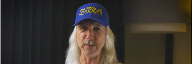 Image is Scarman wearing a Scarman blue baseball hat and white Scarman shirt