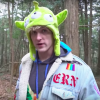 Logan Paul wearing a Toy Story alien hat in a forest