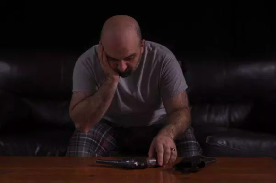 man looking at a gun while sitting on couch