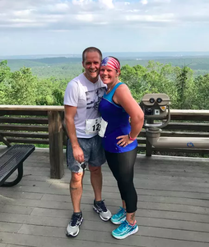 husband and wife stand smiling after completing a race