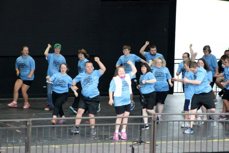Group of people with Down syndrome wearing blue shirts and dancing in unison