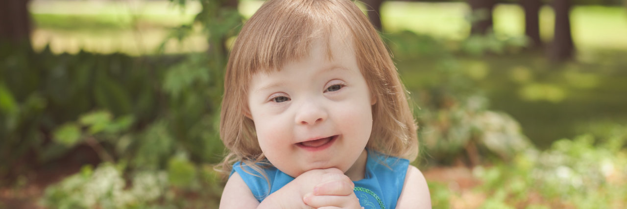 Little girl with Down syndrome wearing a blue dress and holding her hands together, smiling at camera.