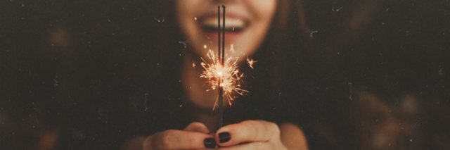 young woman laughing and holding sparkler with only sparkler in focus