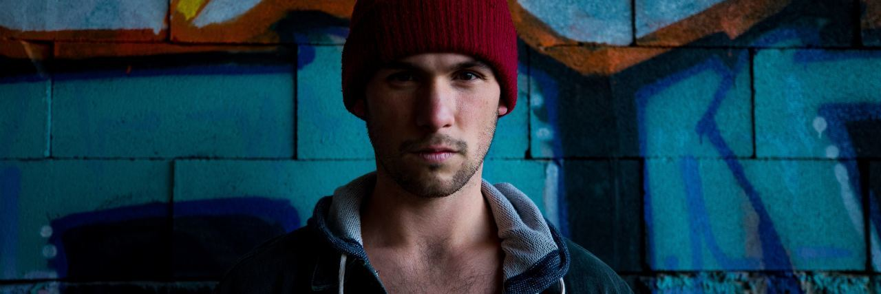 man wearing beanie standing in front of graffiti wall