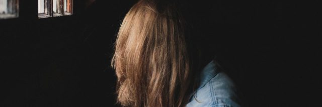 woman in a dark room with her hair covering her face
