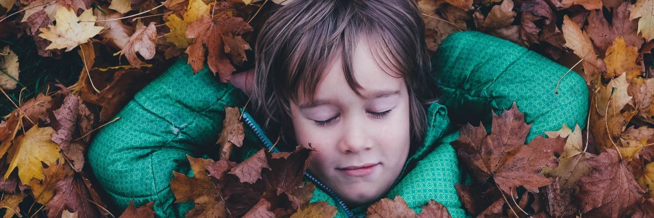 Boy with eyes closed laying in a pile of leaves