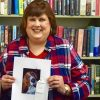 A photo of the writer in a library, holding an illustration of a dog.