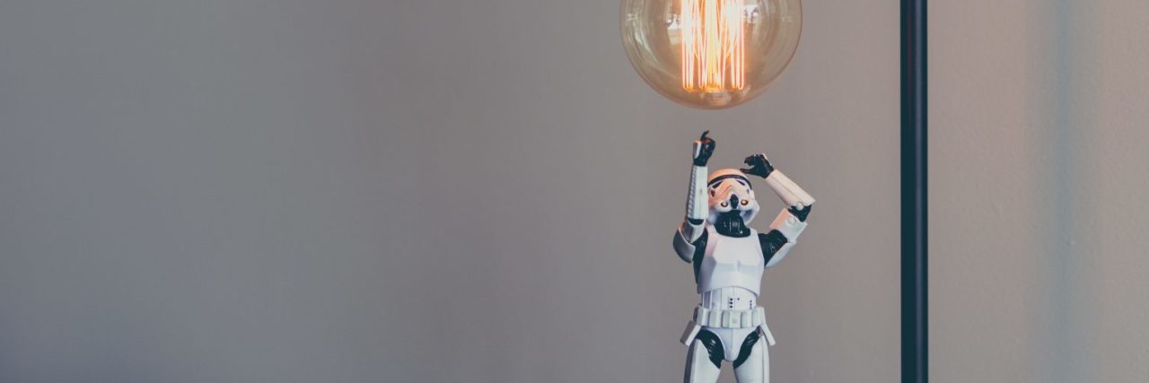 storm trooper star wars toy looking up at edison lightbulb