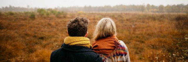 couple embracing in front of misty field in fall or winter