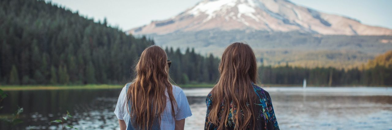 friends sitting in front of lake with mountain in distance