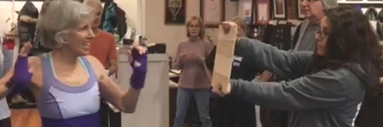 Jean getting ready to break wood in Rock Steady boxing class.