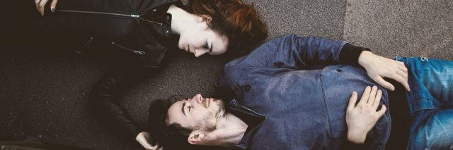 couple laying on pavement looking at one another