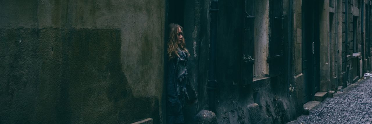 woman standing outside in alleyway in jacket
