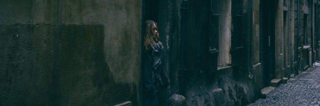 woman standing outside in alleyway in jacket
