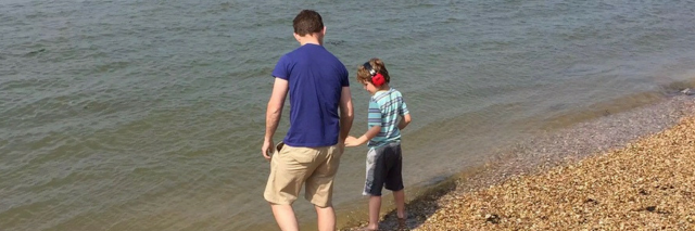 Father and son at the beach by the water. dad is wearng a royal blue shirt and holds his son's hand. Son is wearing red noise cancelling headphones and a striped sky blue shirt.