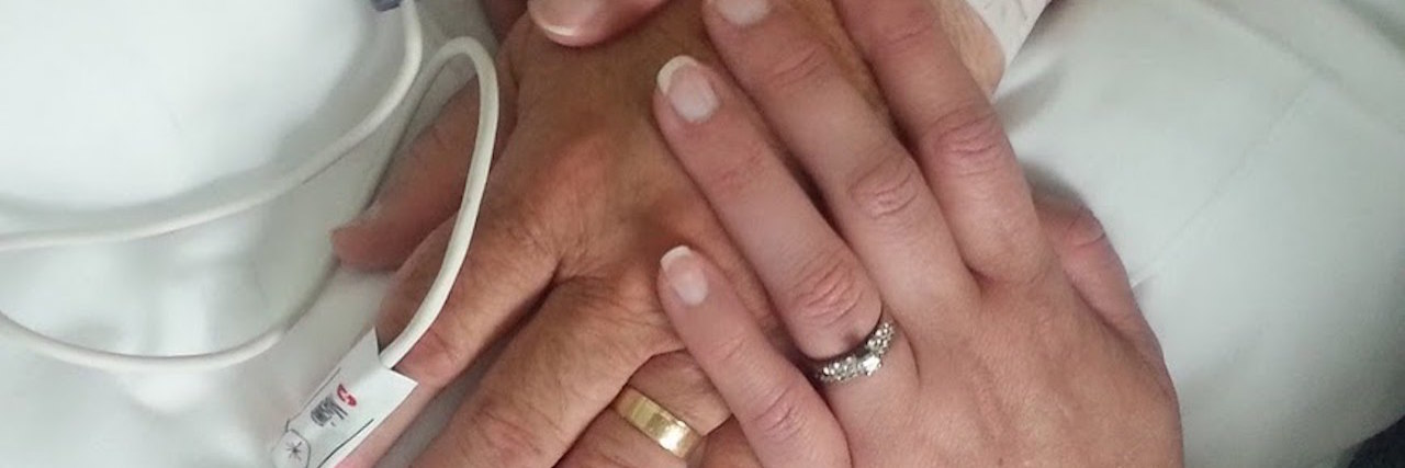 wife holding husband's hand while he lies in a hospital bed connected to monitors