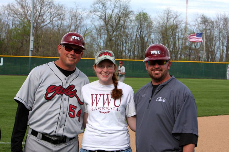 A photo of the writer with the coaches on senior day.