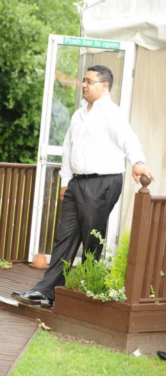 man wearing dress clothes and standing outside in his yard