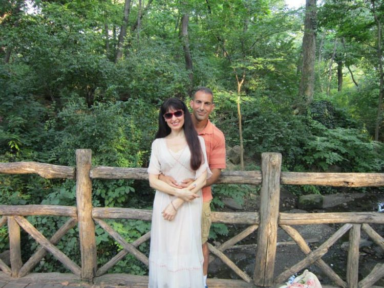 the author and her husband arm in arm with a fence and trees behind them