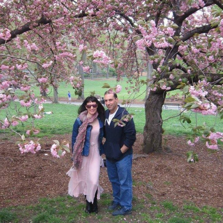 Author and husband standing under a cherry blossom tree
