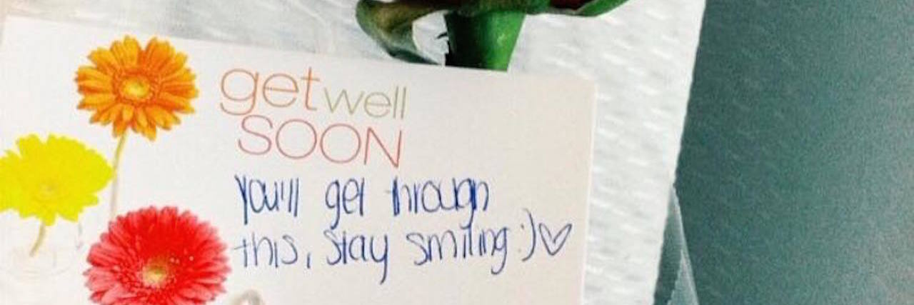 "rose with a card attached saying ""get well soon! you got this, keep on smiling"""