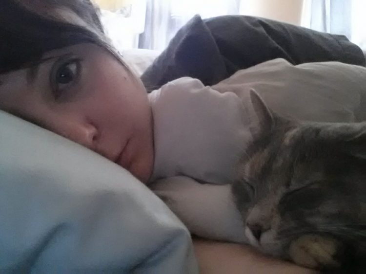 woman lying in bed with cat
