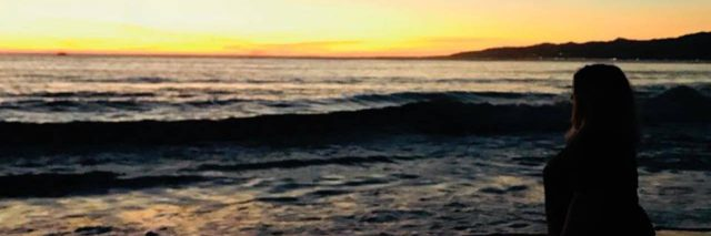 """woman standing on the beach at sunset with the hashtag """"I'll rise up"""""""
