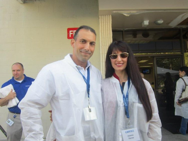 The author and her husband standing with white coats on while visiting Grifols