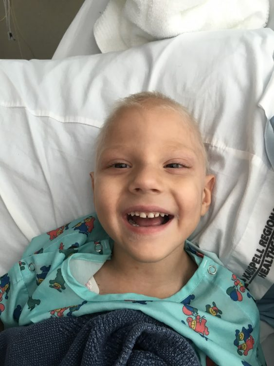 Dax smiling in the hospital without hair