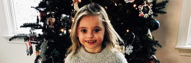 Little girl with Down syndrome standing in front of her Christmas tree and smiling for picture