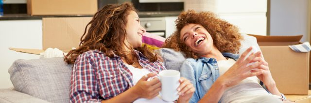 two women relaxing on a couch and laughing