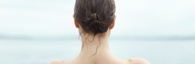 photo of back of woman swimming in the ocean with wet hair