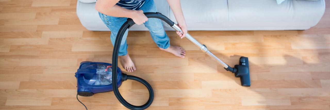 A woman vacuuming a hardwood floor.