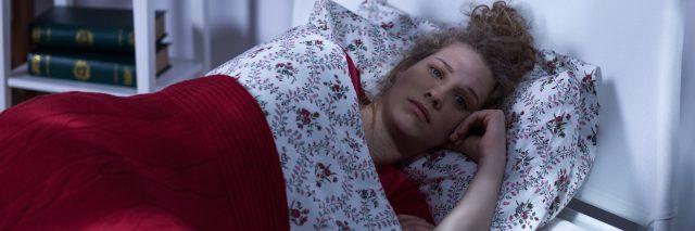 woman lying in bed at night awake