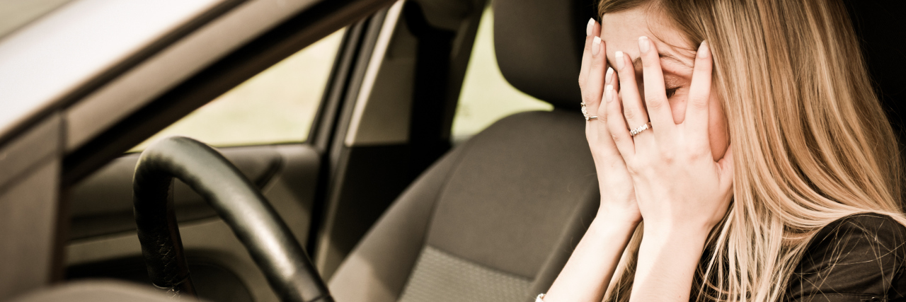 woman in car stressed or upset with hands over face