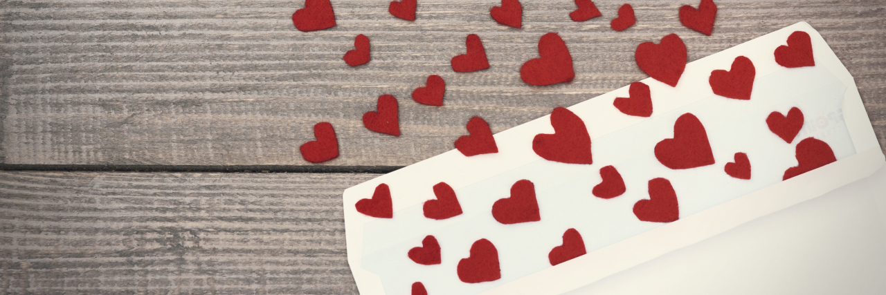 envelope with red hearts spilling out