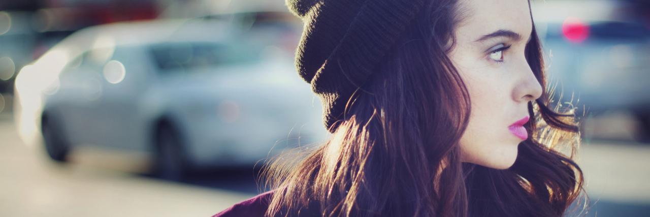 woman wearing a beanie walking outside on the street