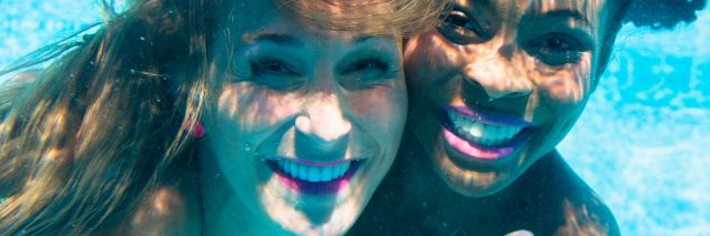 friends diving underwater together and smiling