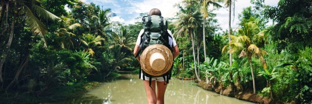 young woman traveling with backpack standing at edge of tropical river