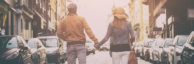 couple walking down a street and holding hands