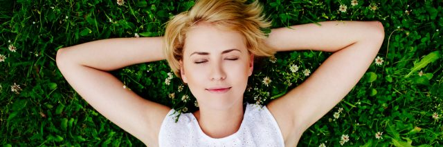 blonde woman in a white dress lying in the grass with her arms behind her head and her eyes closed