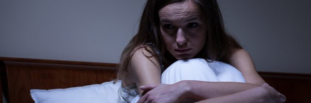 Young worried woman sitting in bed at night