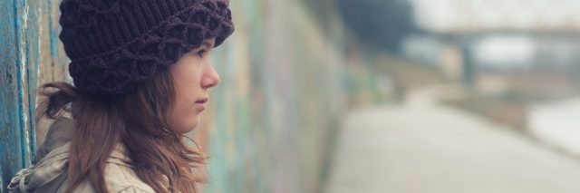 young woman in a white jacket and purple beanie leaning against a wall outside on a cloudy day
