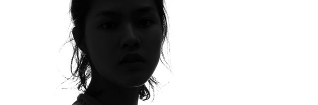 dark silhouette of a woman looking at the camera against a white background